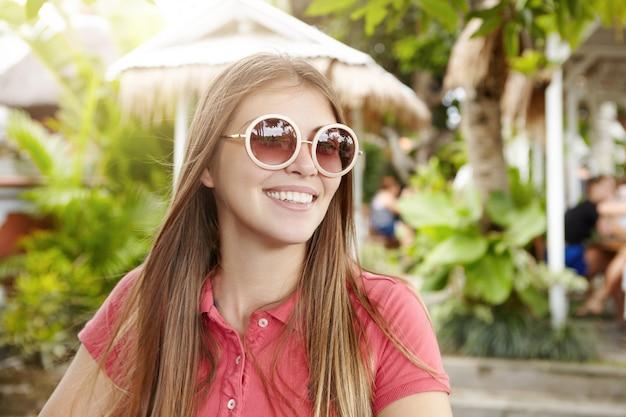 Jolie étudiante portant des lunettes de soleil rondes élégantes souriant joyeusement, profitant d'un temps ensoleillé pendant les vacances dans un pays tropical.