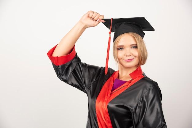 Jolie étudiante posant sur un mur blanc.