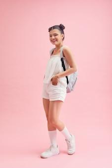 Jolie étudiante le premier jour après les vacances d'été porte une tenue décontractée isolée sur fond rose