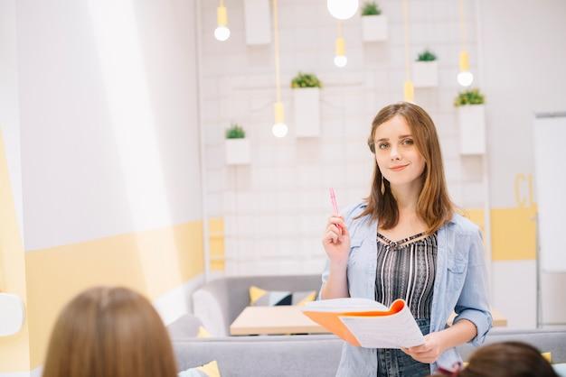 Jolie étudiante tenant le stylo et le cahier