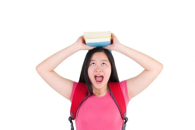 Jolie étudiante universitaire tenant un livre sur la tête