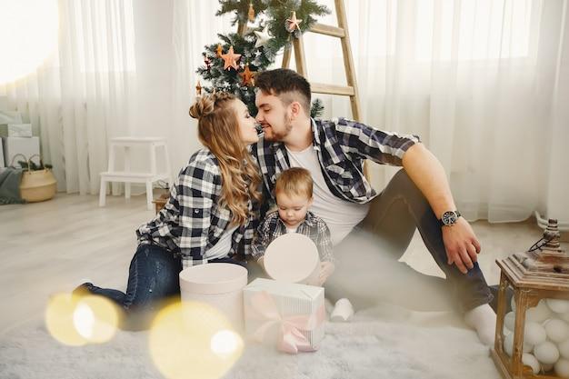 Jolie famille assis près d'un arbre de noël