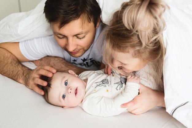 Jolie famille au lit. les parents se moquent de leur bébé