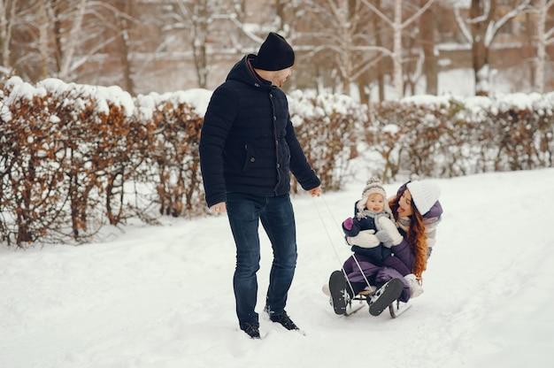 Jolie famille dans un parc d'hiver