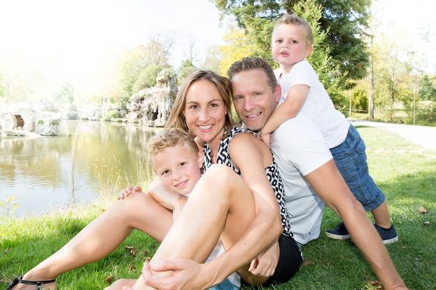 Jolie famille de quatre mère père et fils à l'extérieur en été