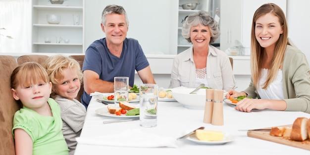 Jolie famille en regardant la caméra tout en mangeant son repas