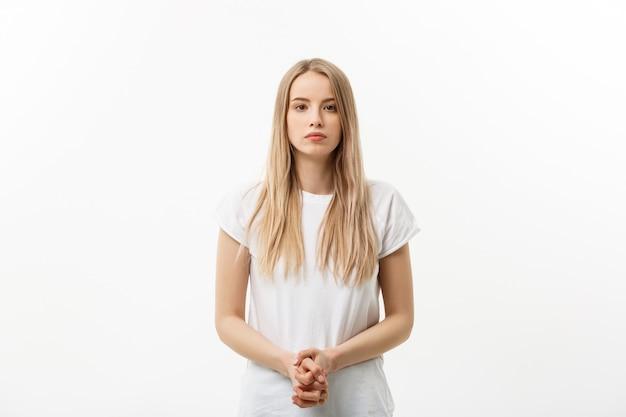 Jolie femelle avec des cheveux blonds, habillée avec désinvolture, regardant avec satisfaction devant la caméra, étant