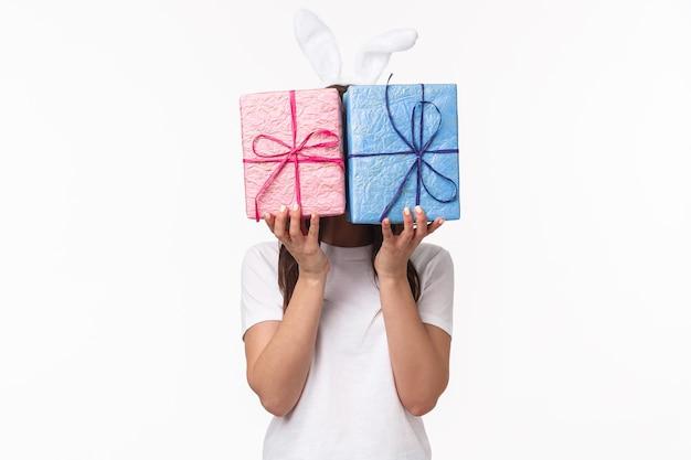 Jolie femelle lapin de pâques dans des oreilles de lapin, cachant son visage derrière des coffrets cadeaux enveloppés de pastel