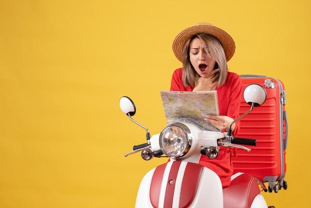Jolie femme abasourdie sur un cyclomoteur avec une valise rouge tenant une carte