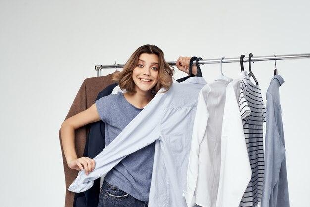 Jolie femme accro du shopping choisissant des vêtements shopping en magasin fond clair