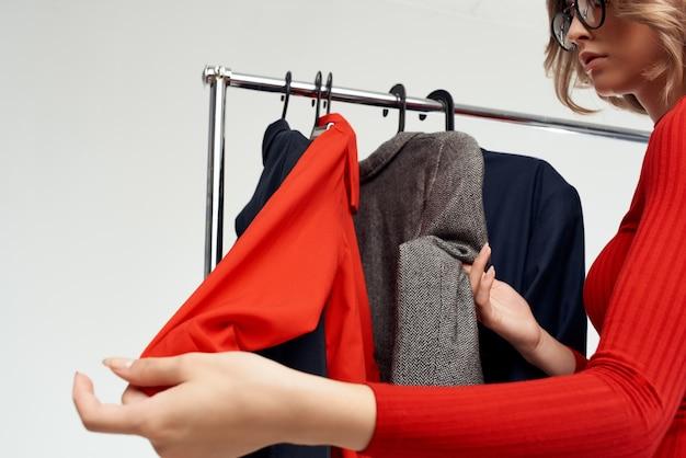 Jolie femme accro du shopping choisissant des vêtements shopping en magasin fond isolé