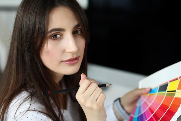 Jolie femme adulte caucasienne, choisir la couleur à l'aide de la palette fantail