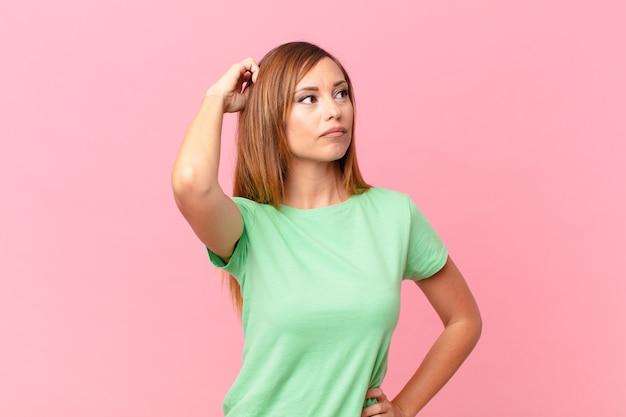 Jolie femme adulte se sentant perplexe et confuse, se grattant la tête