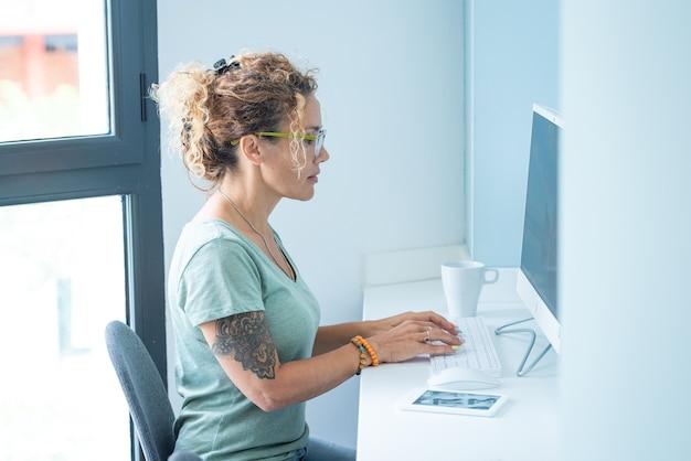 Jolie femme adulte de style moderne tatouée écrit et travaille sur un ordinateur de bureau dans un bureau ou une pièce à la maison - concept de personnes libres et activité professionnelle en technologie en ligne - jolie dame adulte utilise un clavier en blanc