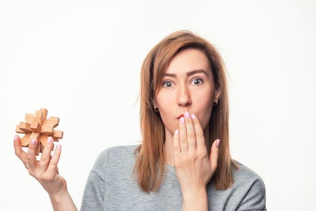 Jolie femme d'affaires de 24 ans à la confusion avec un puzzle en bois.