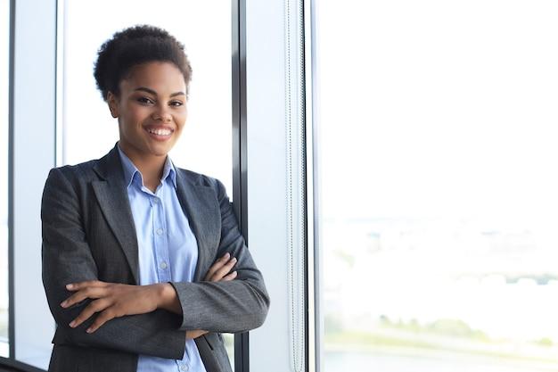 Jolie femme d'affaires afro-américaine regardant la caméra et souriante en se tenant debout au bureau.