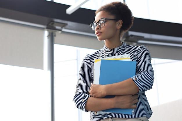 Jolie femme d'affaires afro-américaine souriante en se tenant debout au bureau.