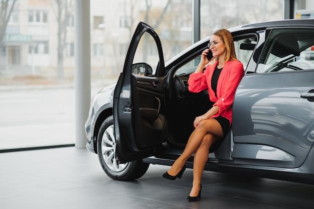 Jolie femme d'affaires assis dans la voiture, parler au téléphone et souriant