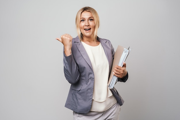 Jolie femme d'affaires aux cheveux blonds portant une veste isolée sur un mur gris, portant des dossiers, pointant vers l'espace de copie