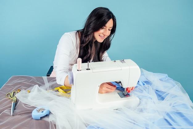 Jolie femme d'affaires brune souriante couturière tailleur (couturière) travaille dans l'atelier avec machine à coudre et ruban à mesurer sur fond bleu dans le studio.