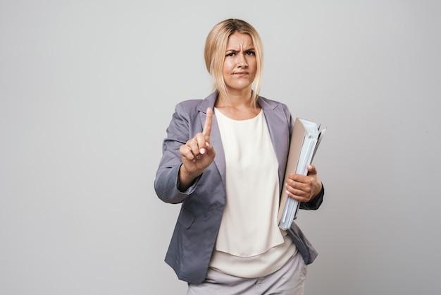 Jolie femme d'affaires en colère aux cheveux blonds perplexe portant une veste isolée sur un mur gris, portant des dossiers, pointant du doigt