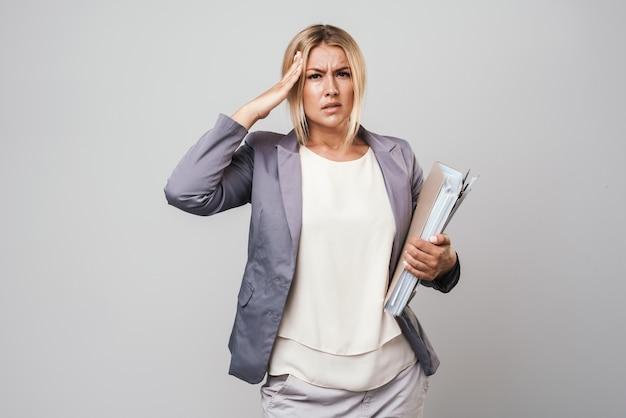 Jolie femme d'affaires confuse aux cheveux blonds mécontente portant une veste isolée sur un mur gris, portant des dossiers
