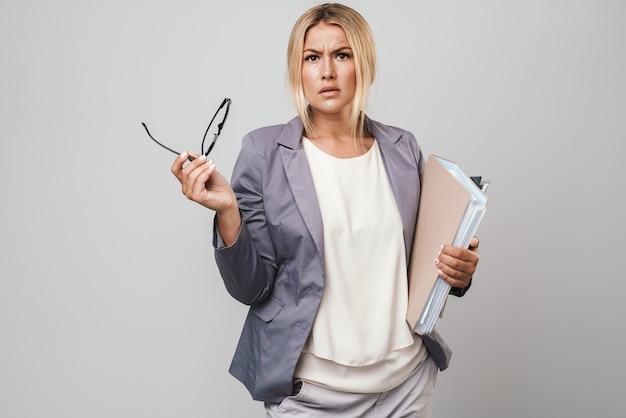 Jolie femme d'affaires confuse aux cheveux blonds portant une veste isolée sur un mur gris, portant des dossiers