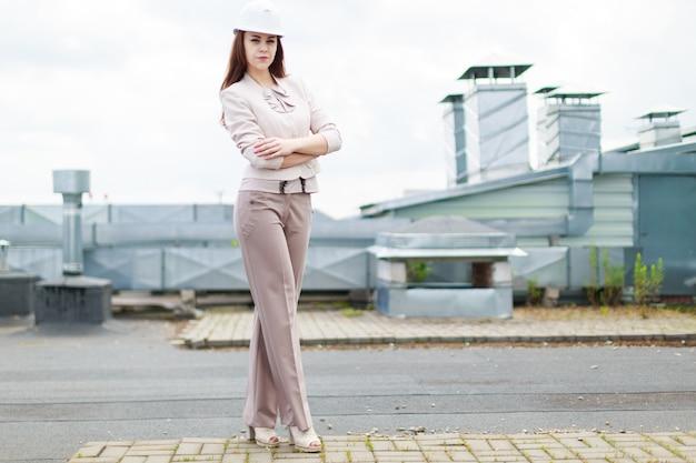 Jolie femme d'affaires en costume beige se tenir sur le toit