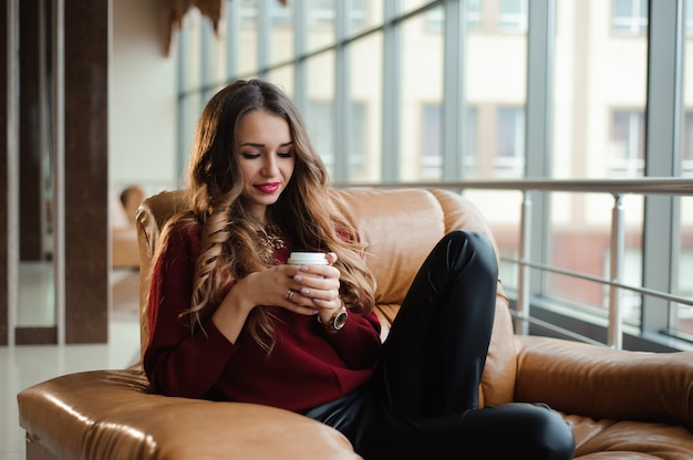 Jolie femme d'affaires dans un pull rouge prendre une pause-café