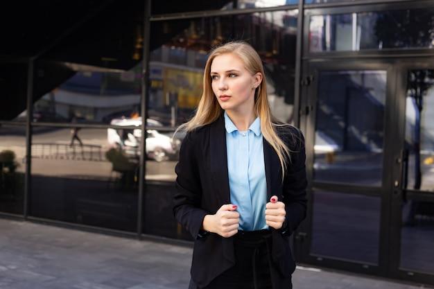 Jolie femme d'affaires devant l'immeuble de bureaux