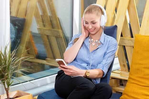 Jolie femme d'affaires écoute de la musique dans un loft moderne. concept de travail indépendant, de détente et de loisirs. femme en affaires. le pigiste du centre de coworking se repose.