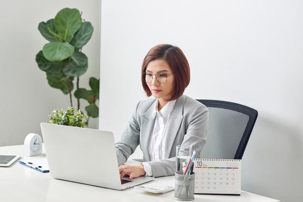 Jolie femme d'affaires est assise au bureau avec ordinateur et calendrier au bureau