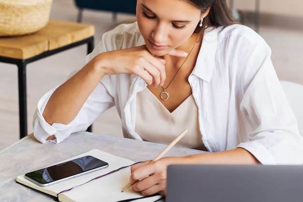 Jolie femme d'affaires est assise à table dans un ordinateur portable, le smartphone se trouve sur la table, prend des notes avec un crayon dans un ordinateur portable.