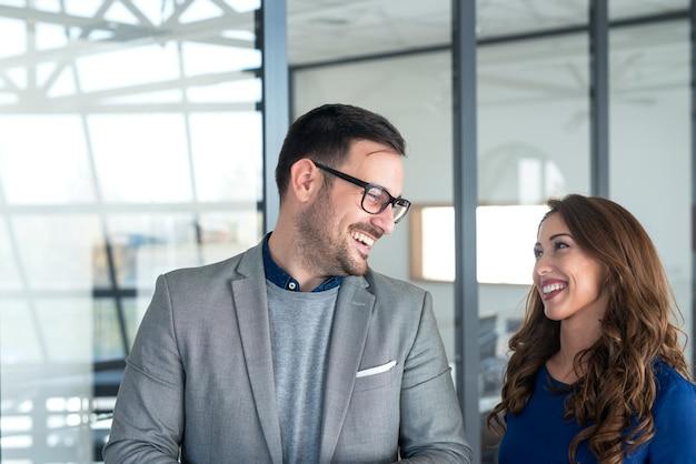 Jolie femme d'affaires et gestionnaire se regardant et souriant.