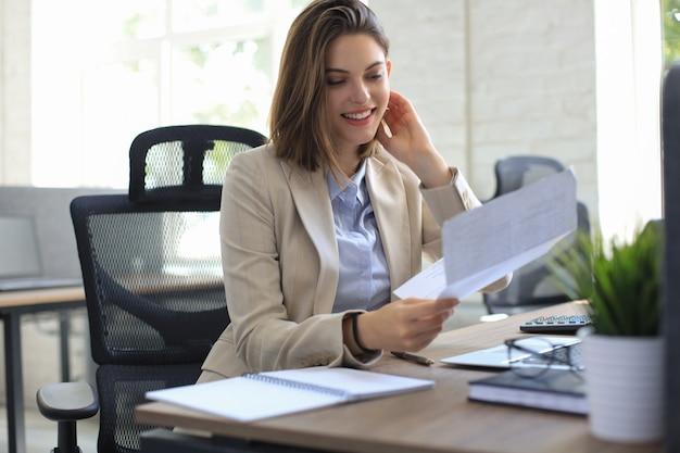 Jolie femme d'affaires joyeuse vérifiant les documents papier au bureau, travaillant sur un ordinateur portable.