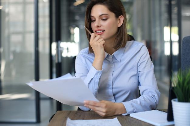 Jolie femme d'affaires joyeuse vérifiant les documents papier au bureau.