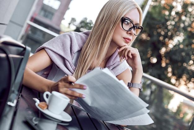 Jolie femme d'affaires lisant des journaux au café de la ville