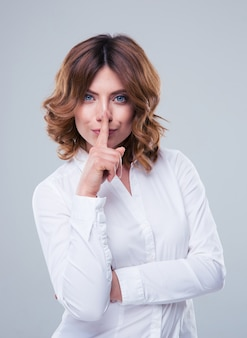 Jolie femme d'affaires montrant le doigt sur les lèvres