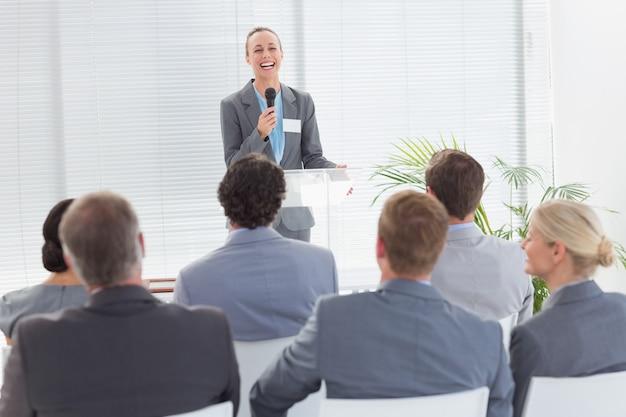 Jolie femme d'affaires parlant au micro pendant la conférence