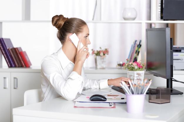 Jolie femme d'affaires parlant au téléphone au bureau.