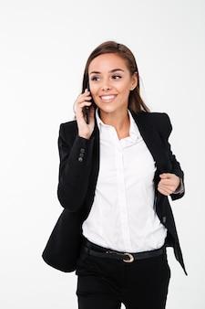 Jolie femme d'affaires, parler par téléphone. en regardant de côté.