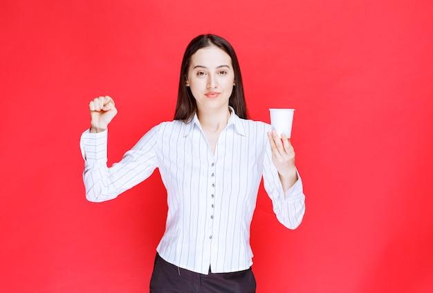 Jolie femme d'affaires posant avec une tasse de thé en plastique sur fond rouge.