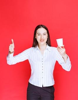 Jolie femme d'affaires posant avec une tasse de thé en plastique et levant les pouces.