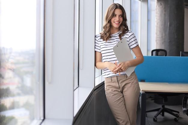 Jolie femme d'affaires regardant la caméra et souriante en se tenant debout au bureau.
