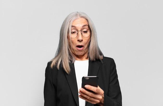 Jolie femme d'affaires senior avec un téléphone intelligent.