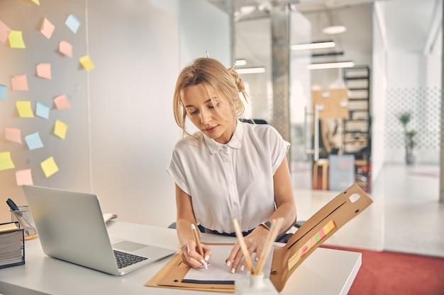 Jolie femme d'affaires signant des papiers tout en étant assise à la table avec un ordinateur portable moderne