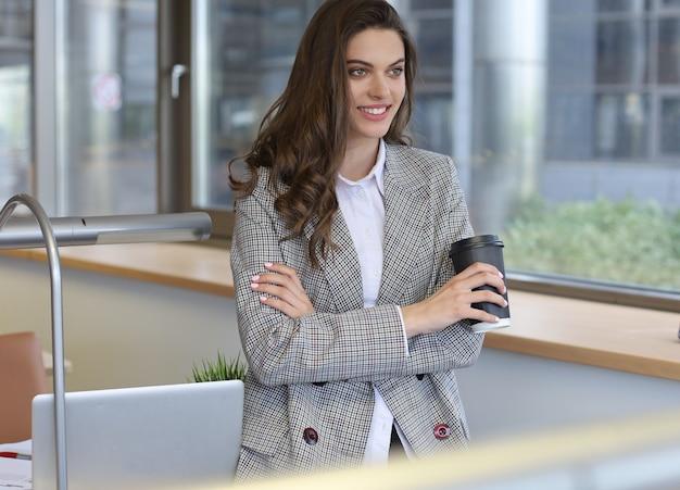 Jolie femme d'affaires souriante debout au bureau avec une tasse de café.