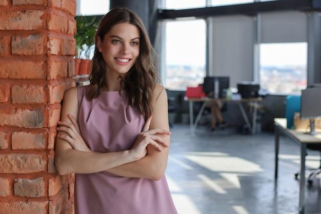 Jolie femme d'affaires souriante en se tenant debout au bureau.