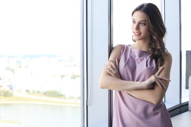 Jolie femme d'affaires souriante en se tenant debout dans le bureau près de la fenêtre.