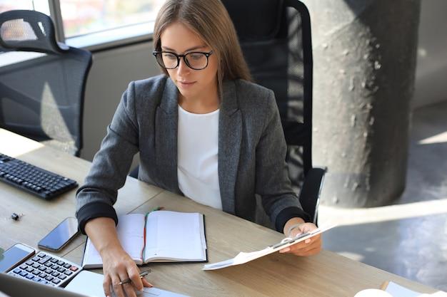 Jolie femme d'affaires tenant des documents et les regardant tout en étant assis au bureau au bureau.